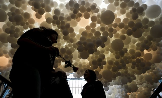 A woman carries a rose as she walks under an art installation made of over 100,000 white balloons by French artist Charles Petillon inside Covent Garden market in London, Britain, August 27, 2015. (Photo by Suzanne Plunkett/Reuters)