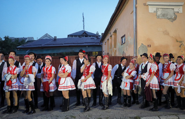 Youngsters wearing traditional costumes wait before a march marking one year since the death of Nobel laureate and Holocaust survivor Elie Wiesel in Sighetu Marmatiei, northern Romania, Sunday, September 10, 2017. Hundreds marched on Sunday in Wiesel's Romanian hometown, the scene of mass deportation of Jews to Nazi death camps in 1944. (Photo by Vadim Ghirda/AP Photo)