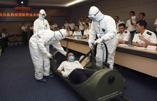Health inspection officers help a mock patient (C) get into a negative pressure isolation stretcher, during a drill to demonstrate the procedures of transporting an Ebola victim, at Shenzhen Entry-exit Inspection and Quarantine Bureau, in Shenzhen, Guangdong province August 14, 2014. China's quarantine authority has intensified inspections at customs to prevent the deadly Ebola virus, which killed over 1,000 people in Africa, from entering the country, Xinhua News Agency reported. (Photo by Reuters/Stringer)