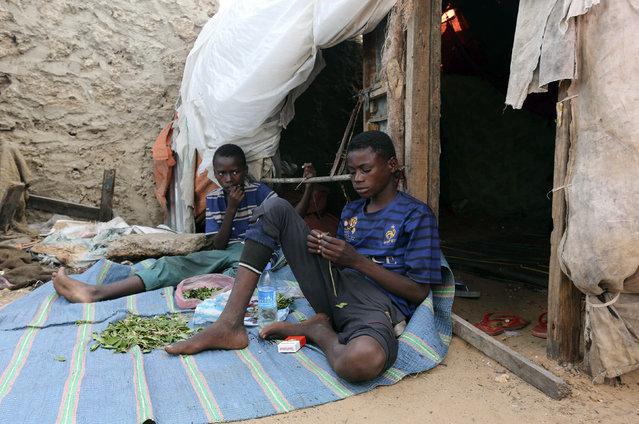 Ali Abdi (R), 14, and his friend Abdulahi Yaroow, 13, chew khat, in Mogadishu August 10, 2014. (Photo by Thomas Mukoya/Reuters)