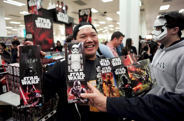 """A shopper shows off his haul of new merchandise from the upcoming film """"Star Wars: The Force Awakens"""" at a department store open just after midnight on """"Force Friday"""" in Sydney, September 4, 2015. (Photo by Jason Reed/Reuters)"""