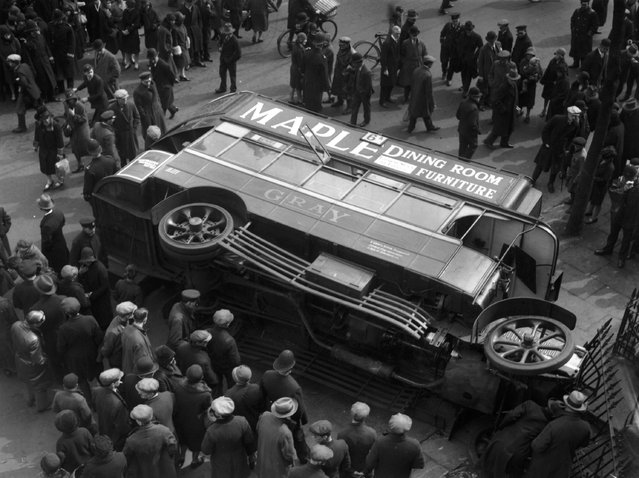 A crowd of passers-by gather round an overturned bus in Shirland Road, London, circa 1925. (Photo by Topical Press Agency)