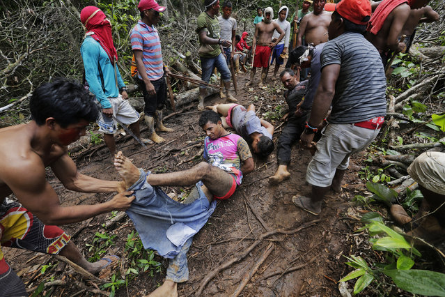 Ka'apor Indian warriors tie up and remove the pants of loggers during a jungle expedition to search for and expel them from the Alto Turiacu Indian territory, near the Centro do Guilherme municipality in the northeast of Maranhao state in the Amazon basin, August 7, 2014. (Photo by Lunae Parracho/Reuters)