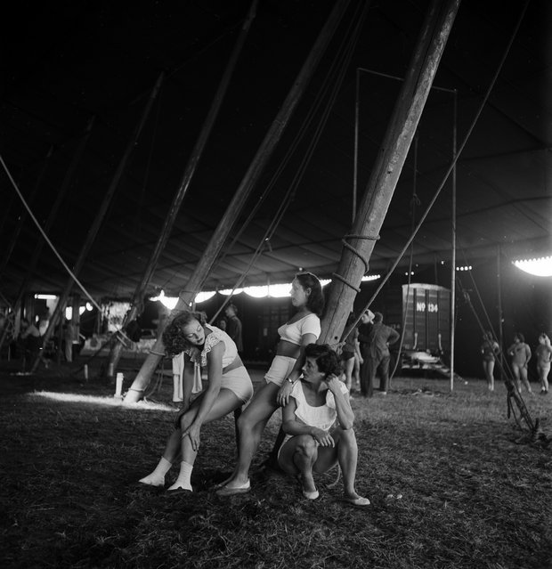 Three circus girls relaxing near a pole during a rehearsal for the Ringling Bros. and Barnum & Bailey Circus in Sarasota, FL in 1949. (Photo By Nina Leen/Time Life Pictures/Getty Images)