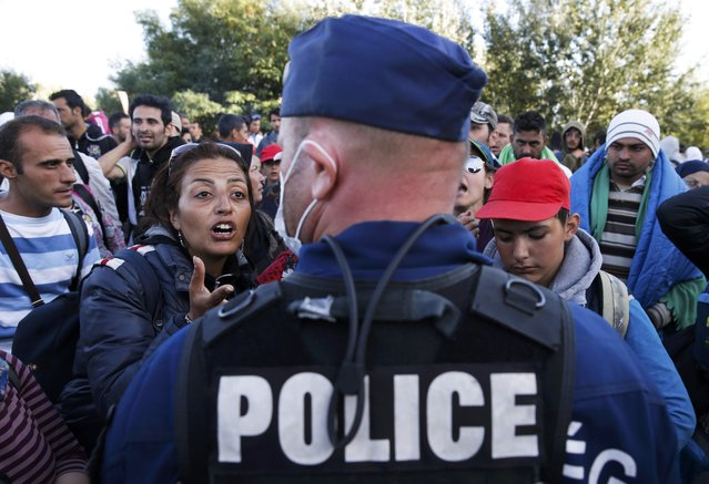 Migrants address a Hungarian police officer at collection point in the village of Roszke, Hungary, September 7, 2015. (Photo by Marko Djurica/Reuters)