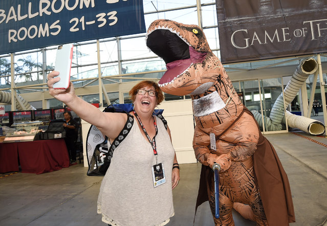 "Inger Utke, left, takes a selfie with Edwin Galarza, dressed as a ""Star Wars"" themed dinosaur, during Preview Night at Comic-Con International held at the San Diego Convention Center, Wednesday, July 20, 2016, in San Diego. (Photo by Denis Poroy/Invision/AP Photo)"
