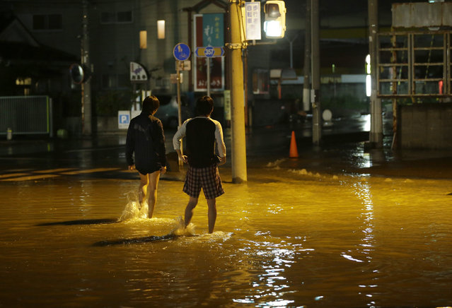 People walk through a flooded street in Joso, Ibaraki prefecture, north of Tokyo, Thursday, September 10, 2015. Raging floodwaters broke through a flood berm Thursday and swamped the city north of Tokyo, washing away houses, forcing dozens of people to rooftops to await helicopter rescues. (Photo by Shizuo Kambayashi/AP Photo)