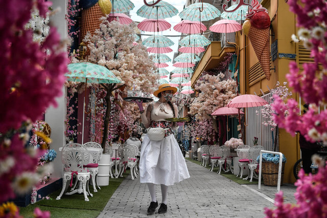 A waitress wearing a home made protective floral mask and pink gloves serves clients at a thematic outdoor cafe in Athens on May 29, 2020, as cafes, bars and restaurants reopen after a two-month-long closure aimed at stemming the spread of the COVID-19 pandemic, caused by the novel coronavirus. (Photo by Louisa Gouliamaki/AFP Photo)