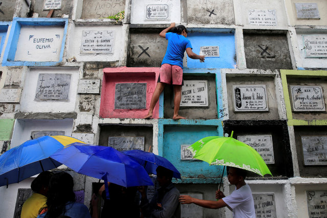People visit apartment-style tombs of their loved ones during the observance of All Saints' Day at Navotas Public cemetery in Metro Manila, Philippines, November 1, 2017. (Photo by Romeo Ranoco/Reuters)