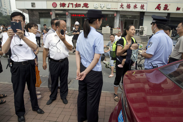 Yuan Shanshan, third right, the wife of detained Chinese lawyer Xie Yanyi, carries her child as she talks to a police officer while other plain clothes security personnel film journalists near the Tianjin No. 2 Intermediate People's Court in northern China's Tianjin Municipality on Tuesday, August 2, 2016. The court in the northern Chinese city of Tianjin has begun to try the first of four human rights advocates charged with subversion of state power, marking the first publicly acknowledged hearing in a yearlong case shrouded in secrecy and involving hundreds of Chinese human rights activists. (Photo by Ng Han Guan/AP Photo)