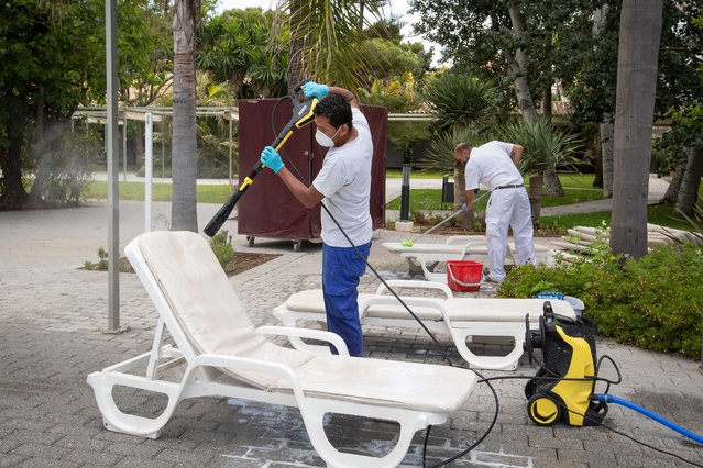 Employees disinfect the loungers at swimming pool area of the RIU Bravo Hotel in Palma de Mallorca on June 10, 2020 as the Balearic Islands prepare to welcome German tourists from June 15 as a test before Madrid reopens international borders on July 1. (Photo by Jaime Reina/AFP Photo)