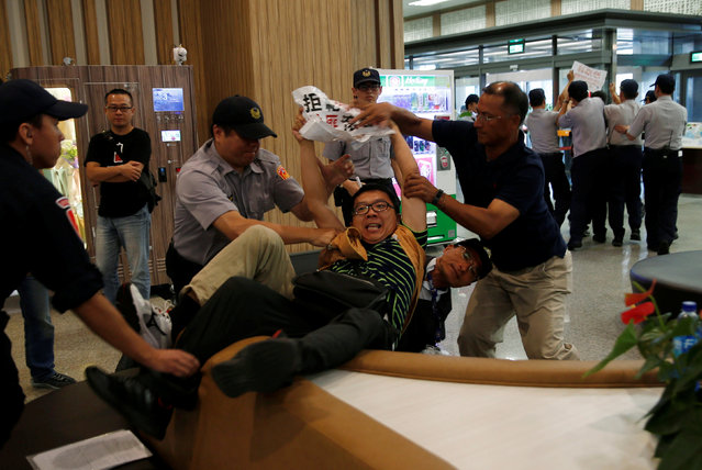 Anti-China demonstrators are stopped by police as Sha Hailin, a member of Shanghai's Communist Party standing committee, arrives in Taiwan for a forum, at Songshan Airport in Taipei August 22, 2016. (Photo by Tyrone Siu/Reuters)
