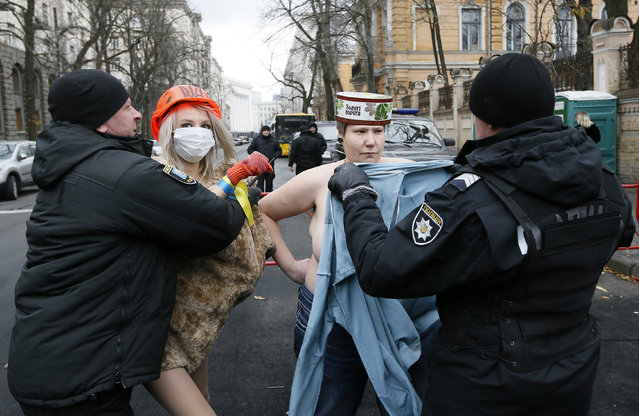 Policemen detain topless activists of women's rights group Femen, who stage a performance during a protest against Ukrainian President Petro Poroshenko and the government while marking the Day of Dignity and Freedom near the presidential administration headquarters in Kiev, Ukraine November 21, 2017. (Photo by Valentyn Ogirenko/Reuters)
