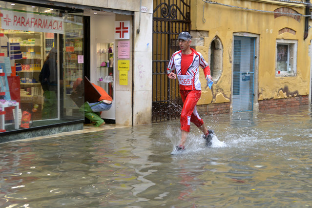 A man runs in a flooded street during a 'acqua alta' on November 11, 2012 in Venice. Rain and wind hit the north of Italy on Sunday and the folooding reached 150 centimetres in Venice. (Photo by Marco Sabadin/AFP Photo)