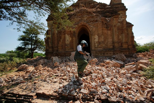 A photograper walks outside a collapsed pagoda after an earthquake in Bagan, Myanmar August 25, 2016. (Photo by Soe Zeya Tun/Reuters)