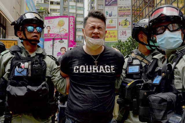 Police detain a protester after spraying pepper spray during a protest in Causeway Bay before the annual handover march in Hong Kong, Wednesday, July. 1, 2020. (Photo by Vincent Yu/AP Photo)
