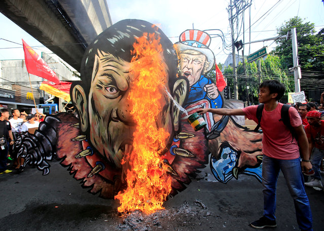 An activist pours gasoline as an effigy of President Rodrigo Duterte and U.S. President Donald Trump burns during a protest action against Duterte's plan to set up a Revolutionary Government, along a street in metro Manila, Philippines November 30, 2017. (Photo by Romeo Ranoco/Reuters)
