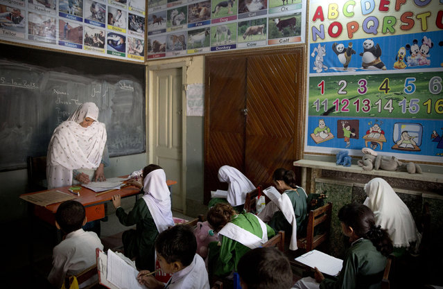In this Saturday, October 5, 2013 file photo, Pakistani children attend class in a school in Mingora, Swat Valley, Pakistan. (Photo by Anja Niedringhaus/AP Photo)