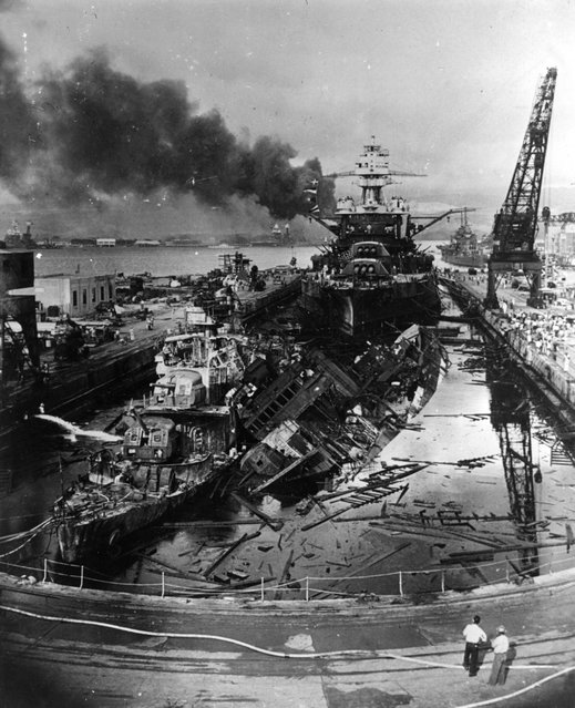 December 1941:  The jumbled mass of wreckage in front of the battleship USS Pennsylvania constitutes the remains of the destroyers USS Downes and USS Cassin, bombed by the Japanese during the raid on Pearl Harbour (Pearl Harbor). The ships were in drydock. The torpedo-damaged cruiser USS Helena is in the right distance, beyond the crane. Visible in the centre distance is the capsized USS Oklahoma with USS Maryland alongside.  (Photo by Fox Photos/Getty Images)