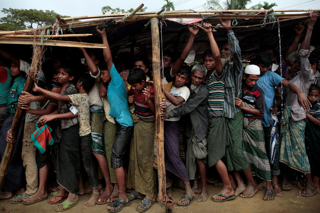Rohingya refugees jostle as they line up for a blanket distribution under heavy rainfall at the Balukhali camp near Cox's Bazar, Bangladesh December 11, 2017. (Photo by Alkis Konstantinidis/Reuters)