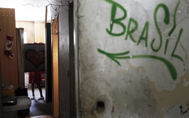 A member of Brazil's Movimento dos Sem-Teto (Roofless Movement) uses a board to gain privacy in one of the 11 empty buildings that the movement took over recently, in the centre of Sao Paulo, December 4, 2012. According to City Hall, there are some 400,000 people in need of stable housing, including the 4,000 families of the Roofless Movement who are squatting in abandoned or vacant buildings that range from apartment blocks to hotels, in Sao Paulo, the largest city in South America. (Photo by Nacho Doce/Reuters)