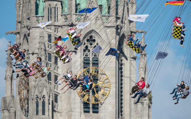 Visitors enjoy a ride on a ferris wheel at the 182nd annual Oktoberfest, backdropped by St. Pauls cathedral in Munich, Germany, October 2, 2015. The world's largest folk and beer festival runs from Sept. 19 to Oct. 4. (Photo by Matthias Balk/EPA)