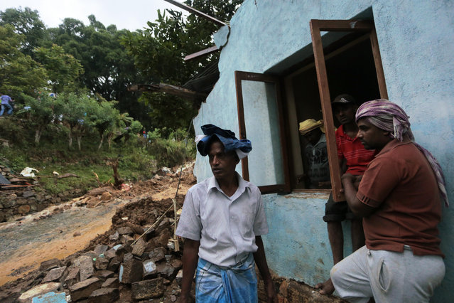 Sri Lankan men stand by their damaged house caused by mudslide at the Koslanda tea plantation in Badulla district, about 220 kilometers (140 miles) east of Colombo, Wednesday, October 29, 2014. (Photo by Eranga Jayawardena/AP Photo)
