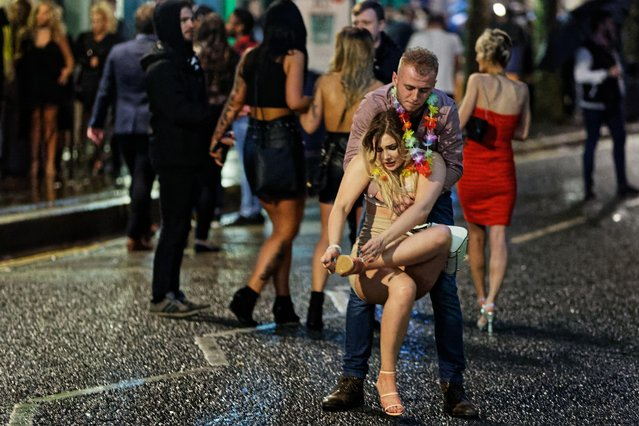 A female clubber struggles with her shoes as she's helped across the road in Swansea, Wales, England, England on December 31, 2017. (Photo by Athena Picture Agency)