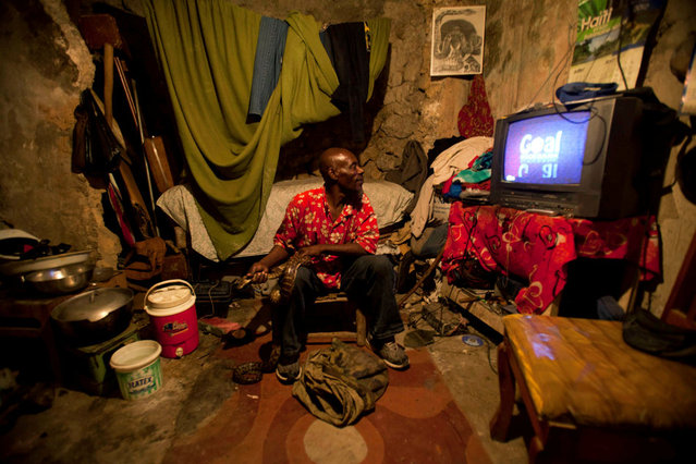 In this January 24, 2013 photo, snake handler Saintilus Resilus watches a soccer game at his home while holding a snake, and a bag of more snakes lays at his feet, as he prepares for his street performances using snakes, for which he charges money, in Petionville, Haiti. Resilus is one of millions of people scrambling to get by in a country where the unemployment rate hovers around 60 percent and most get by on $2 a day. (Photo by Dieu Nalio Chery/AP Photo/Matt Dayhoff)