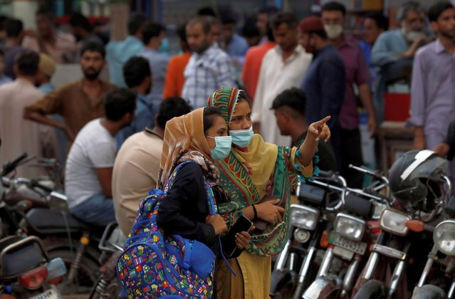 Women wearing protective face masks talk outside a market, as the coronavirus disease (COVID-19) pandemic continues, in Karachi, Pakistan on July 28, 2020. (Photo by Akhtar Soomro/Reuters)