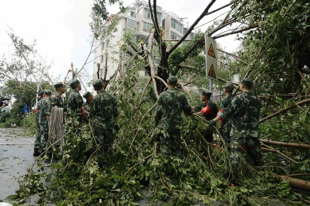 Paramilitary policemen remove toppled trees after Typhoon Meranti swept through Xiamen, Fujian province, China, September 15, 2016. (Photo by Reuters/Stringer)
