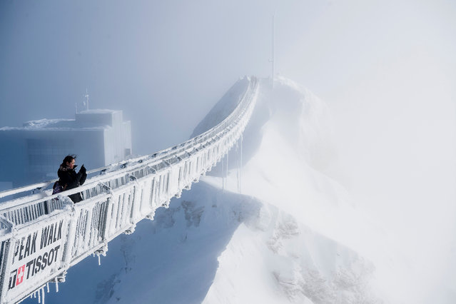 """A tourist walks on the """"Peak Walk"""" suspension bridge on a winter day at the Glacier 3000 on the Col du Pillon between Gstaad and Les Diablerets, in Switzerland, 20 December 2017. (Photo by Jean-Christophe Bott/EPA/EFE)"""