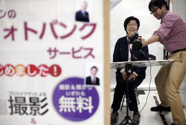 A woman smiles as she is shown her photographic portrait which will be used at her funeral during an end-of-life seminar held by Japan's largest retailer Aeon Co in Tokyo October 24, 2014. (Photo by Toru Hanai/Reuters)