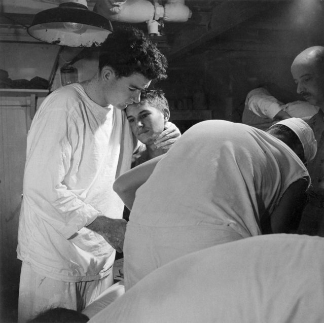 """Pvt. J.B. Slagle, USA, receives his daily dressing of wounds on board USS SOLACE enroute from Okinawa to Guam, May 1945"". (Photo by Lt. Victor Jorgensen)"