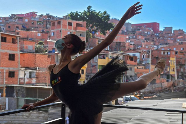 Mariana Sousa, student of the Ballet Paraisopolis, warms up during a rehearse in Paraisopolis favela, outskirts of Sao Paulo, Brazil on August 27, 2020, amid the new coronavirus COVID-19 pandemic. The 200 ballet students of Paraisopolis, the second largest favela in Sao Paulo, restarted rehearsals after five months with a coreography about a police operation that put their community in mourning last year. (Photo by Nelson Almeida/AFP Photo)