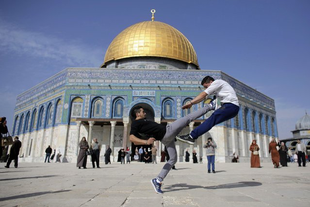 The Dome of the Rock is seen in the background as Palestinian youths practice their parkour skills during Friday prayers in Jerusalem's Old City November 14, 2014. Israel and the Palestinians have pledged to take concrete steps to calm tensions around Jerusalem's holiest site, U.S. Secretary of State John Kerry said on Thursday after talks in the Jordanian capital. (Photo by Ammar Awad/Reuters)