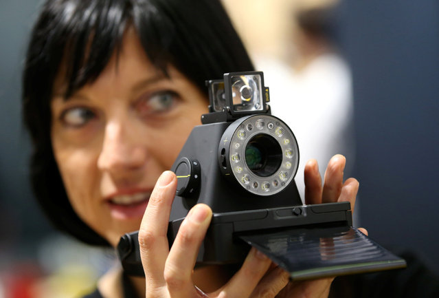A woman takes a picture with the Impossible I-1 analog instant camera, the first new camera system working with the original Polaroid photo format, at the booth of the Impossible project on the Photokina, the world's largest fair for imaging in Cologne, Germany, September 20, 2016. (Photo by Fabrizio Bensch/Reuters)