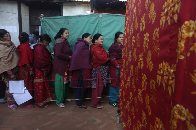 Nepalese women stand and wait on a queue to cast their vote during the legislative elections in Thimi, Bhaktapur, Nepal, Thursday, December 7, 2017. Millions of people in Nepal are voting in the final phase of elections for members of the national and provincial assemblies. About 12 million voters in the southern half of the Himalayan nation are voting Thursday. (Photo by Niranjan Shrestha/AP Photo)