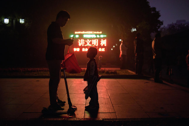 In a photo taken on October 7, 2015 a man opens a drink to a child as they stand before a display board at the entrance to a park in Beijing. (Photo by Ed Jones/AFP Photo)