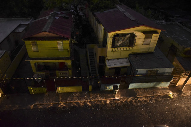 Vehicle lights illuminate a street after a massive blackout, in San Juan, Puerto Rico, Thursday, September 22, 2016. Puerto Ricans faced another night of darkness Thursday as crews slowly restored electricity a day after a fire at a power plant caused the aging utility grid to fail and blacked out the entire island. (Photo by Carlos Giusti/AP Photo)
