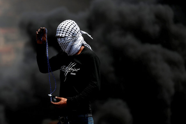 A Palestinian demonstrator uses a sling to hurl stones at Israeli troops during a protest against Jewish settlements, in Kafr Qaddum town in the Israeli-occupied West Bank on September 4, 2020. (Photo by Mohamad Torokman/Reuters)