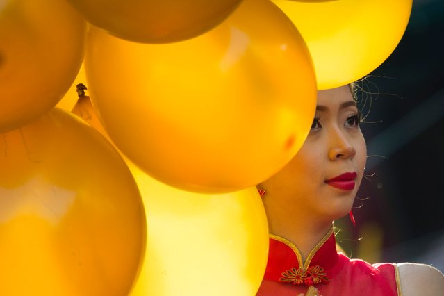 A woman holds balloons during celebrations marking the first day of the Lunar New Year in Yangon's Chinatown district on February 16, 2018. The 2018 Lunar New Year fell on February 16 across much of Asia, marking the start of the Year of the Dog. (Photo by Ye Aung Thu/AFP Photo)