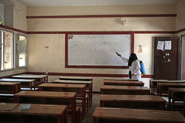 A worker disinfects a classroom as a preventive measure against the spread of the new coronavirus before students taking a final-term school exam at a public school in Sanaa, Yemen, Saturday, August 29, 2020. (Photo by Hani Mohammed/AP Photo)
