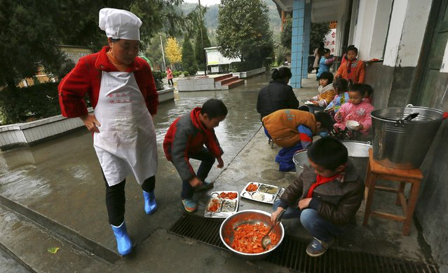 A cook looks on as students fill their plates with food outdoors during lunch time at a primary school in Tongguan village, Liping county, Guizhou province, November 24, 2014. (Photo by Reuters/Stringer)