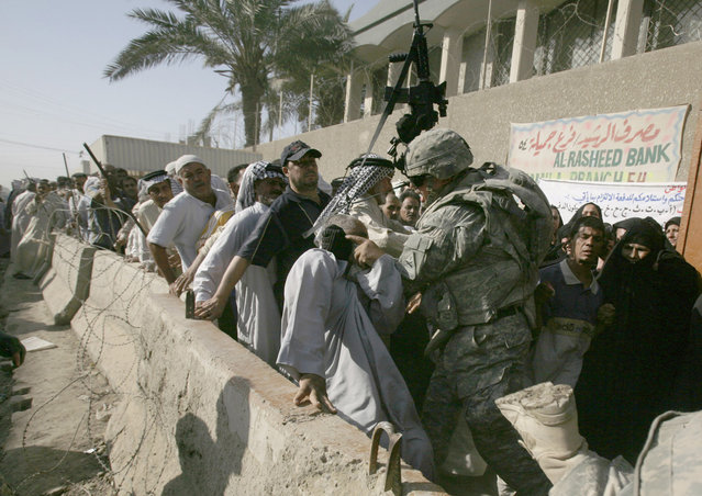 Sgt. Kyle Hale of Yukon, Oklahoma, of 1-6 battalion, 2nd brigade, 1st Armored Division, contains an unruly crowd to protect a man who was nearly trampled, outside the Al Rasheed Bank in the in Jamilah market in Sadr city, Baghdad, on June 10, 2008. (Photo by Petros Giannakouris/AP Photo/The Atlantic)