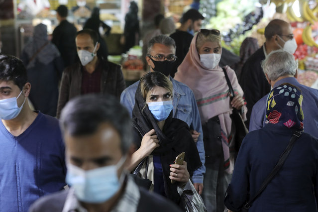 People wear protective face masks to help prevent the spread of the coronavirus in the Tajrish traditional bazaar in northern Tehran, Iran, Thursday, October 15, 2020. Eight months after the pandemic first stormed Iran, pummeling its already weakened economy and sickening officials at the highest levels of its government, authorities appear just as helpless to prevent its spread. (Photo by Ebrahim Noroozi/AP Photo)