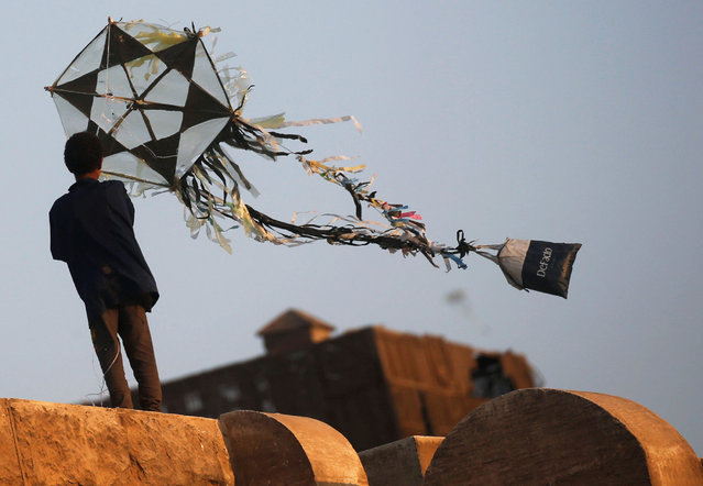 A boy flies a handmade kite from a roof, following the outbreak of the coronavirus disease (COVID-19). in Old Cairo, Egypt on July 26, 2020. (Photo by Amr Abdallah Dalsh/Reuters)