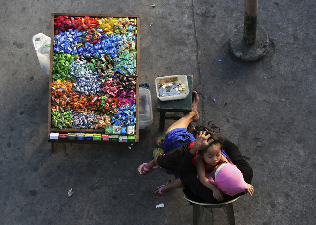 A woman arranges the hair of a girl as they sell candies and cigarettes beside a street in metropolitan Manila, Philippines on Friday, March 2, 2018. Makeshift stalls of street vendors are common along pedestrian lanes in the crowded capital. (Photo by Aaron Favila/AP Photo)