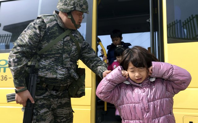 Elementary students exit a vehicle to enter a shelter during a civil defense drill against a possible attack by North Korea on Baeknyeong Island, close to North Korea, in the western waters of South Korea, Tuesday, March 19, 2013. The United States is flying nuclear-capable B-52 bombers on training missions over South Korea to highlight Washington's commitment to defend an ally amid rising tensions with North Korea, Pentagon officials said Monday. (Photo by Bae Jung-hyun/AP Photo/Yonhap)