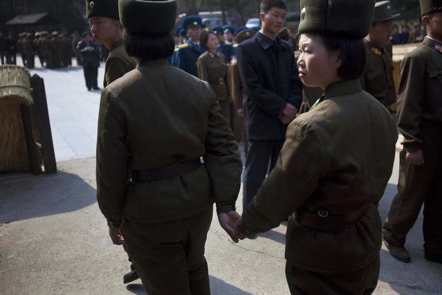 In this April 13, 2011 photo, two female North Korean soldiers hold hands as they tour the birthplace of Kim Il Sung at Mangyongdae, North Korea. (Photo by David Guttenfelder/AP Photo)